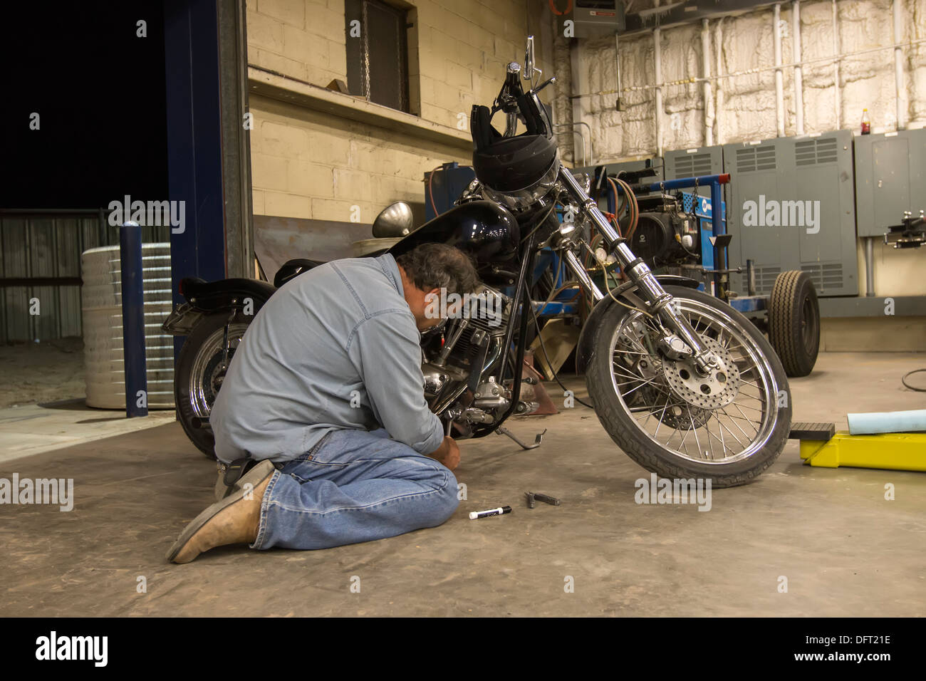 Man working on an American-made motorcycle in a mechanic garage. - Stock Image