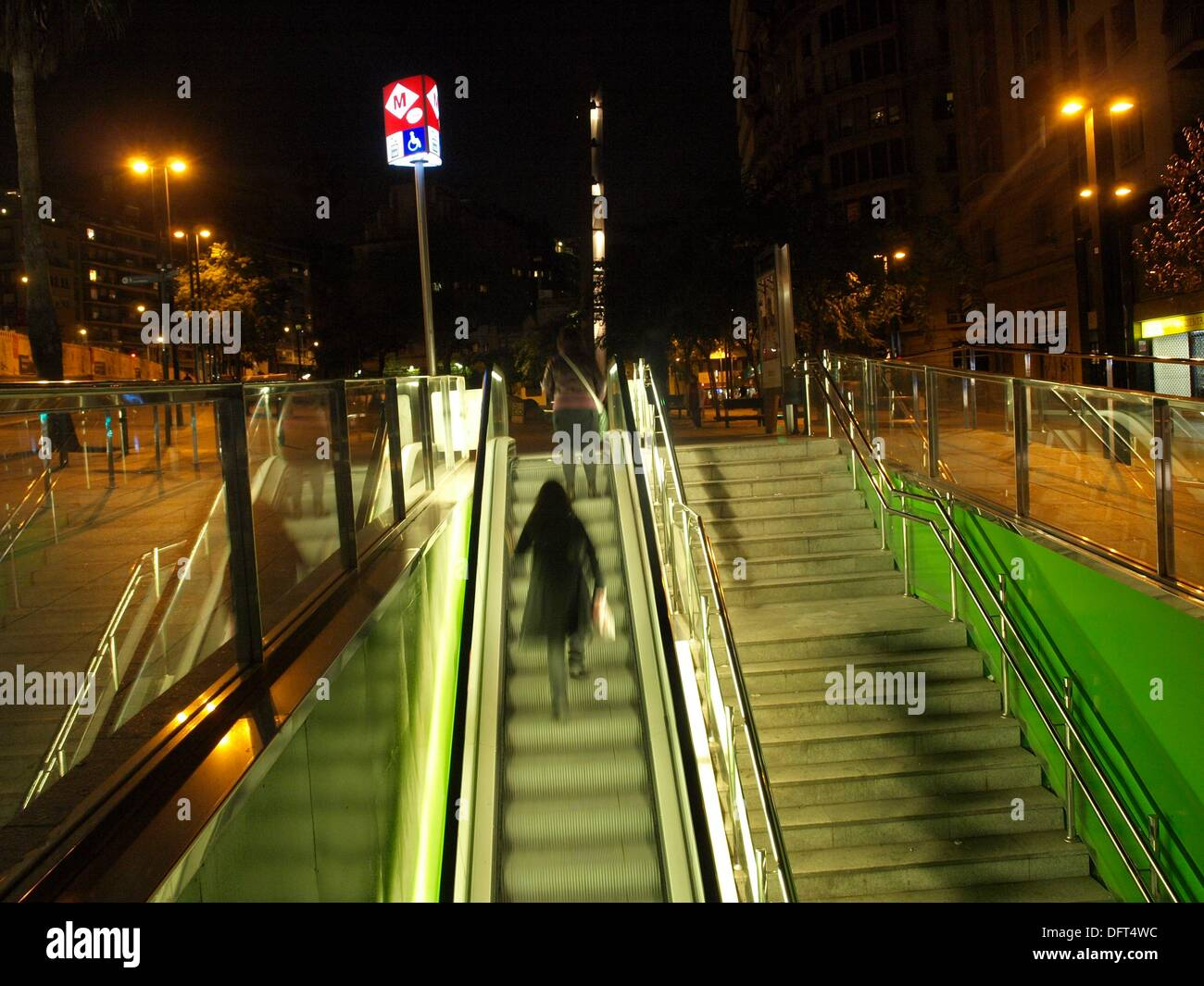 Woman carrying a white bag walking up the escalator of a tube stop at night, Plaça de Lesseps subway station (L3, green line), - Stock Image