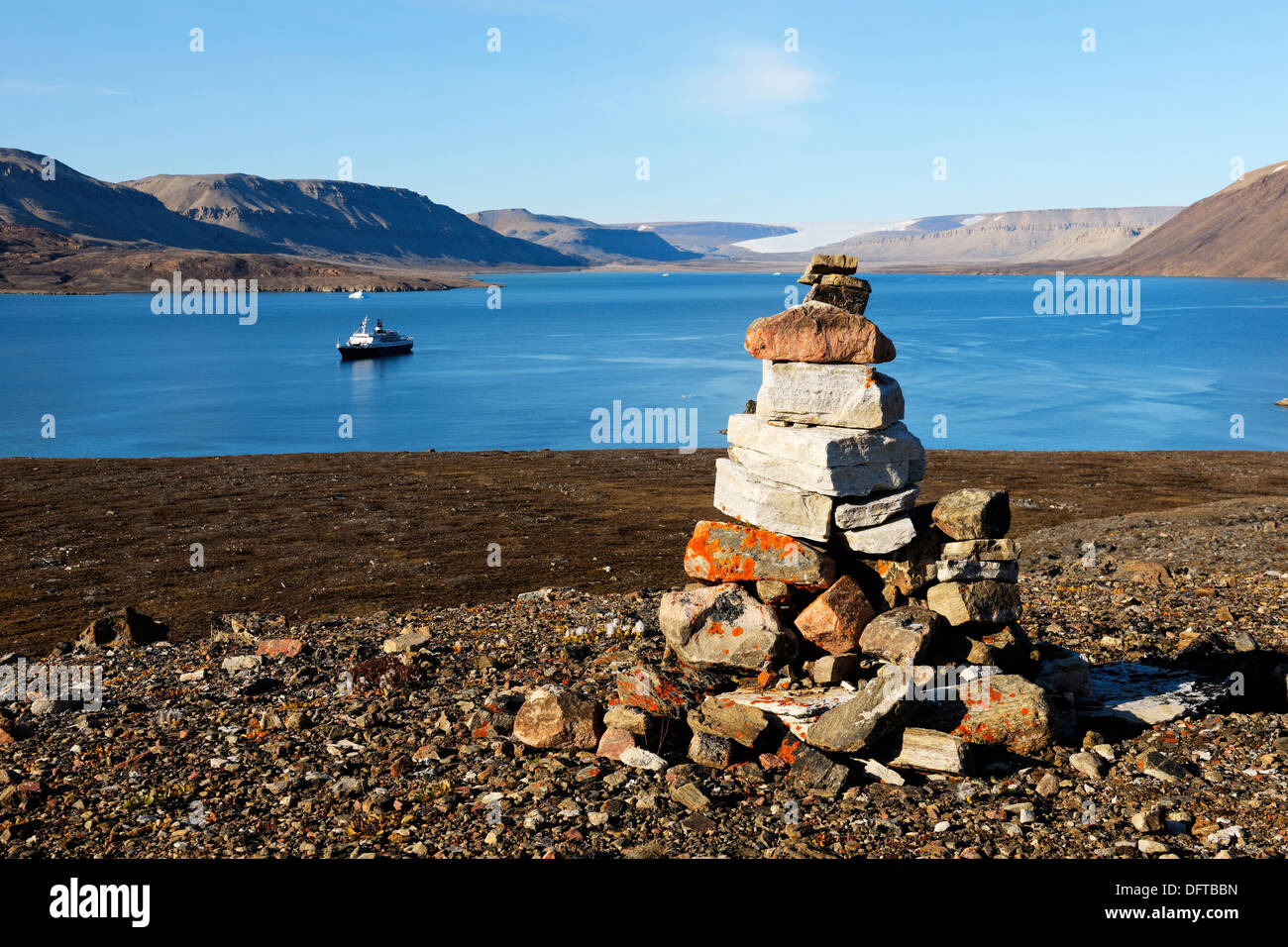 View from an Inukshuk of the Sunshine Fjord and a cruise ship cruising through the sea, Nunavut, Canada - Stock Image