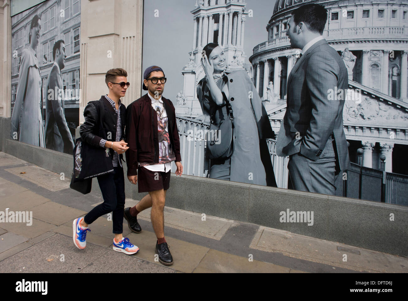 Two men walk past a fashion poster showing a fashion boy and girl and St Paul's Cathedral. - Stock Image