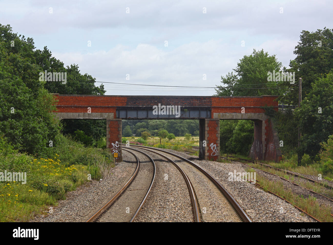 Approaching Padworth road Bridge on the Berks and Hants line looking towards Reading showing an old brick built bridge. - Stock Image