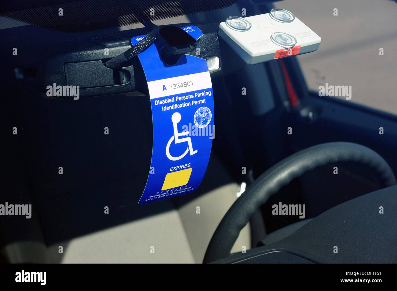 Handicapped permit in the windshield of an automobile - Stock Image