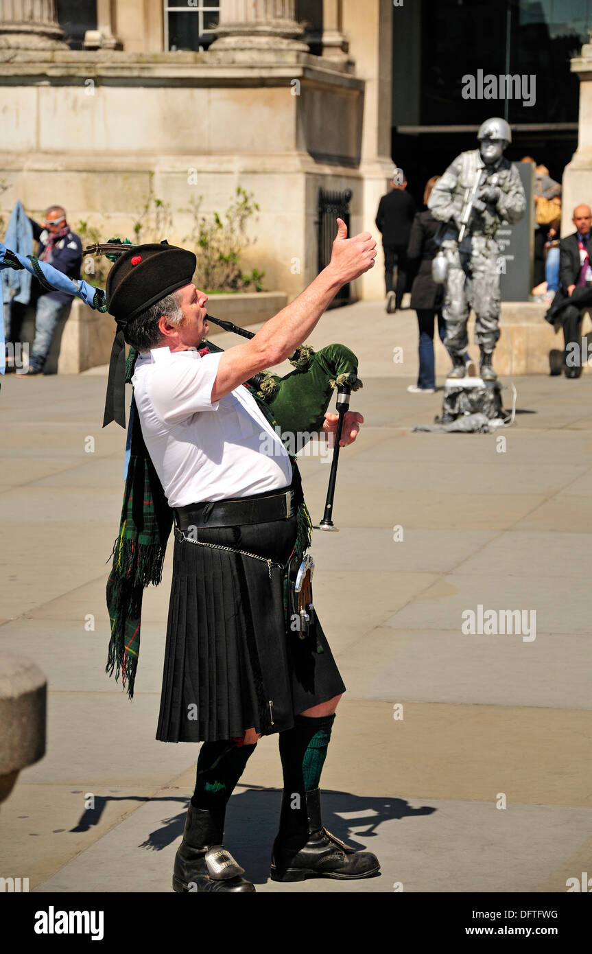 London, England, UK. Scotsman in kilt playing the bagpipes in Trafalgar Square. Human statue behind - Stock Image
