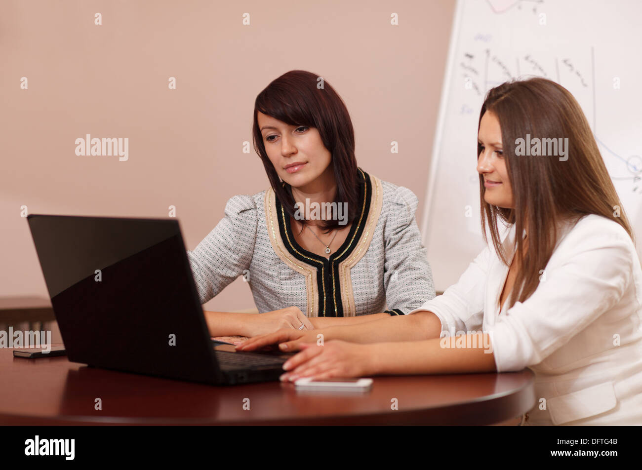 Two women sitting at a table with a laptop - Stock Image