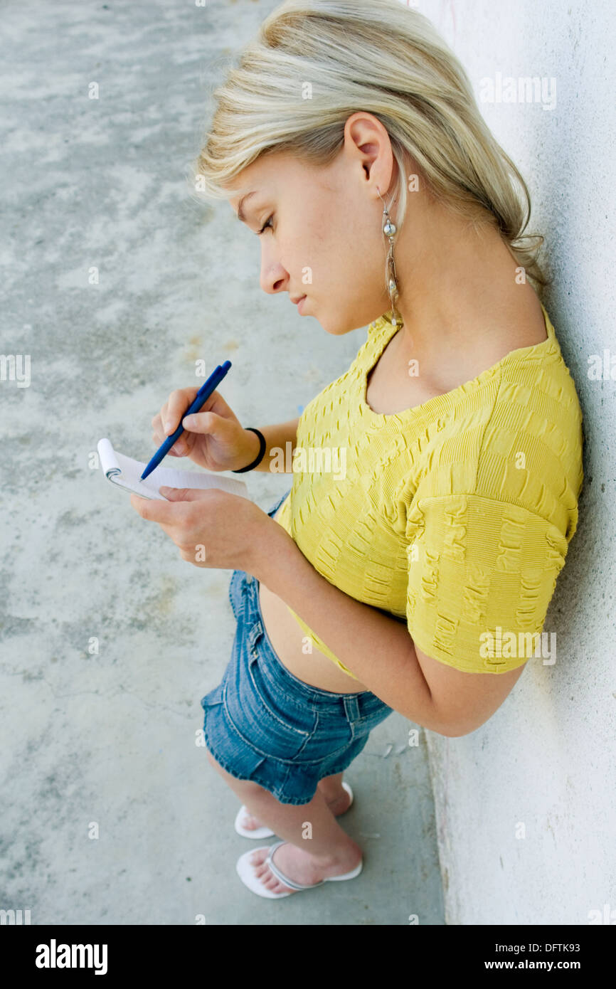 Young girl taking notes - Stock Image