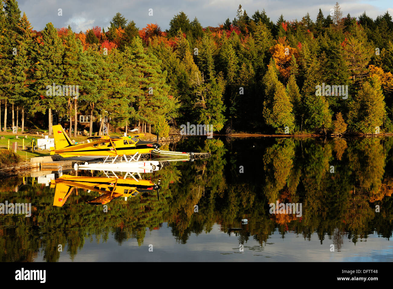 Seaplane on Smoke Lake, in front of a log house in the autumn-coloured forest, Algonquin Provincial Park, Ontario Province - Stock Image