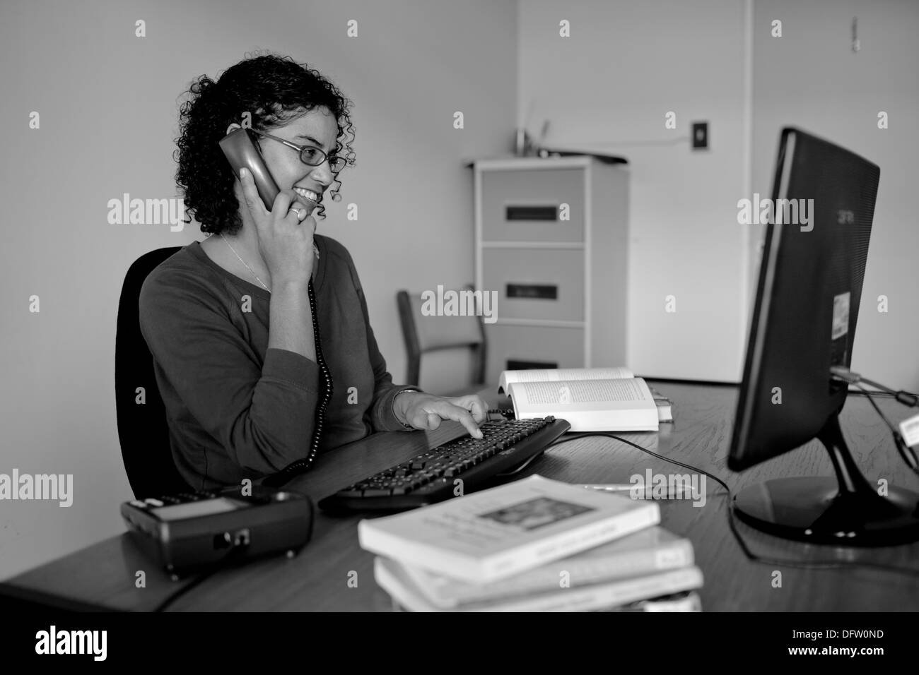 Nicole, postgraduate student talks on the phone and smiles whilst she works on an assignment in her office. - Stock Image
