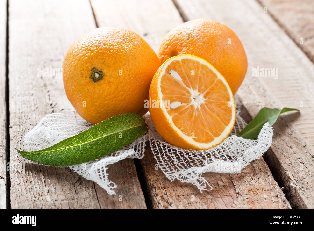 Raw natural oranges on wooden table - Stock Image