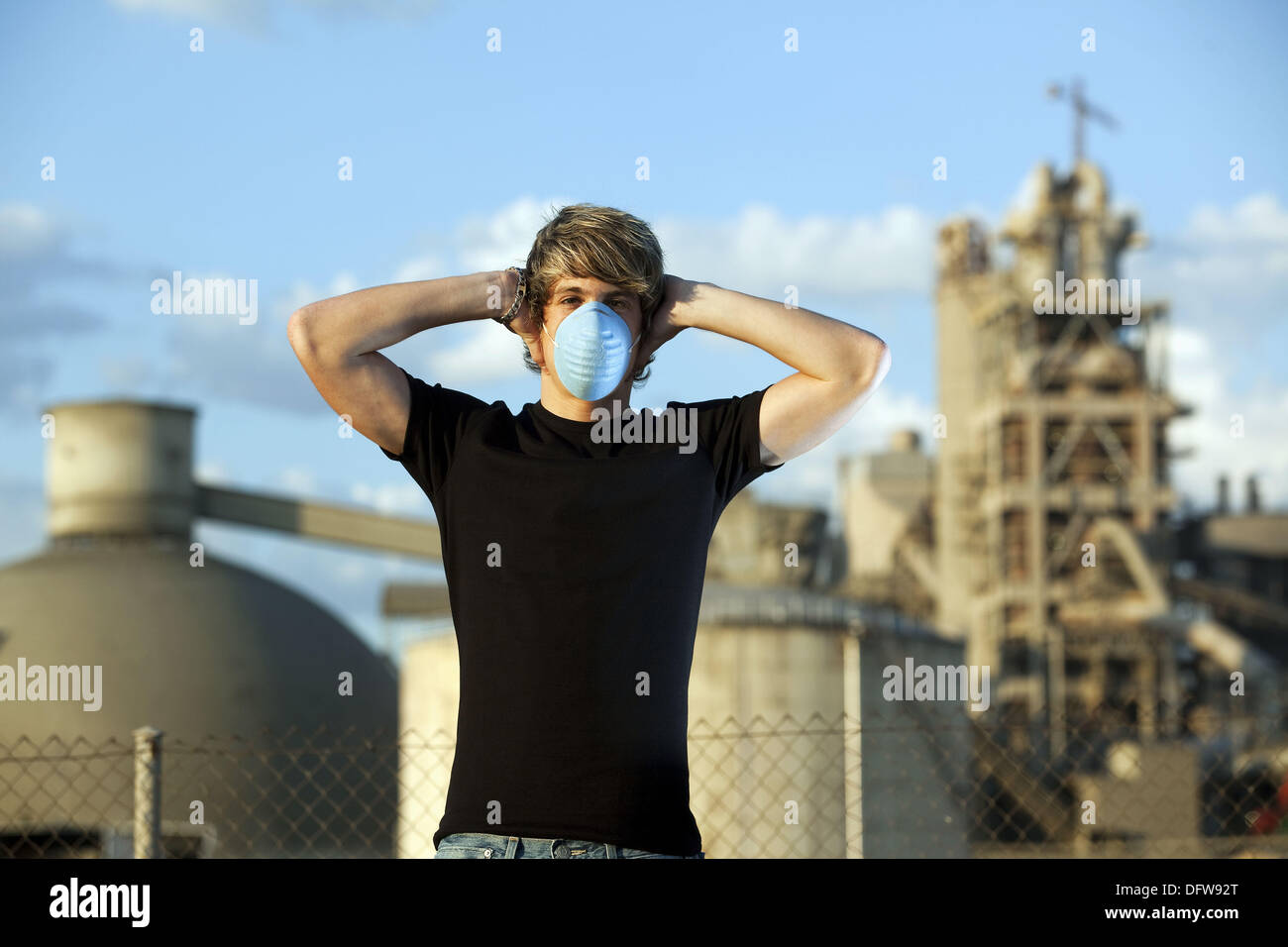 Man with a contamination mask near a cement works Stock Photo