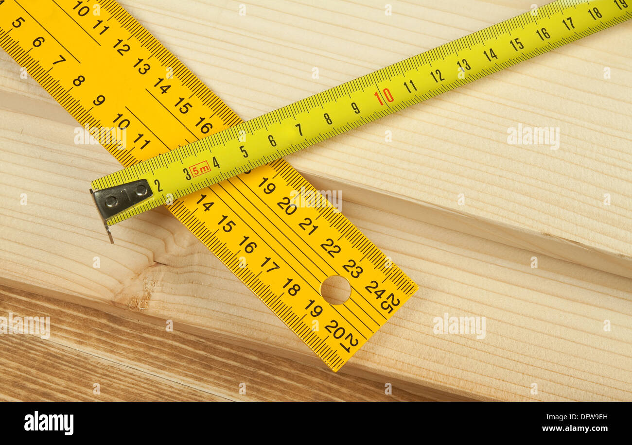 Yellow rulers over wooden background. - Stock Image