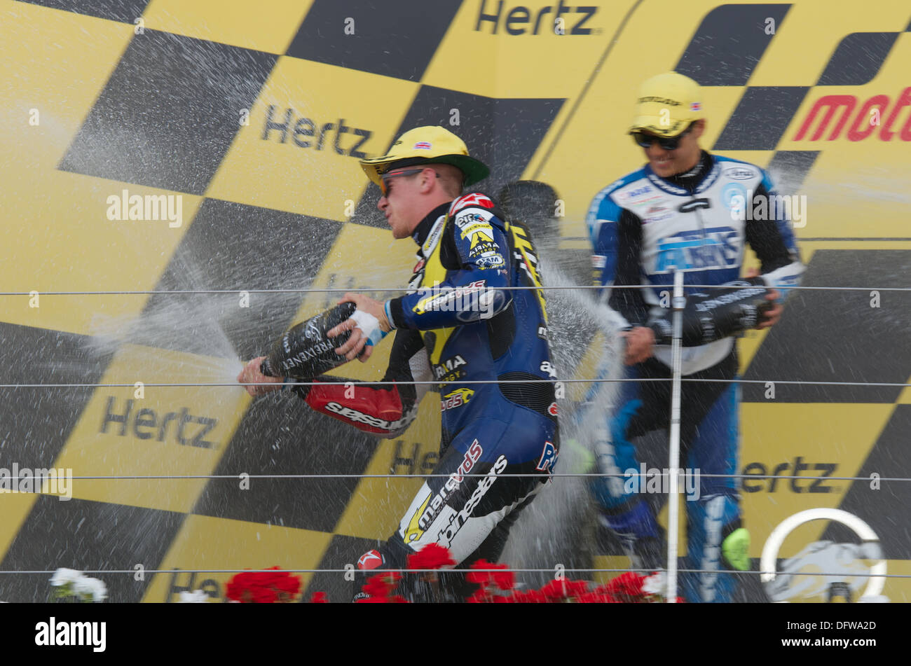 Scott Redding sprays his Champagne on the Silverstone Podium after wining the Moto2 race - Stock Image