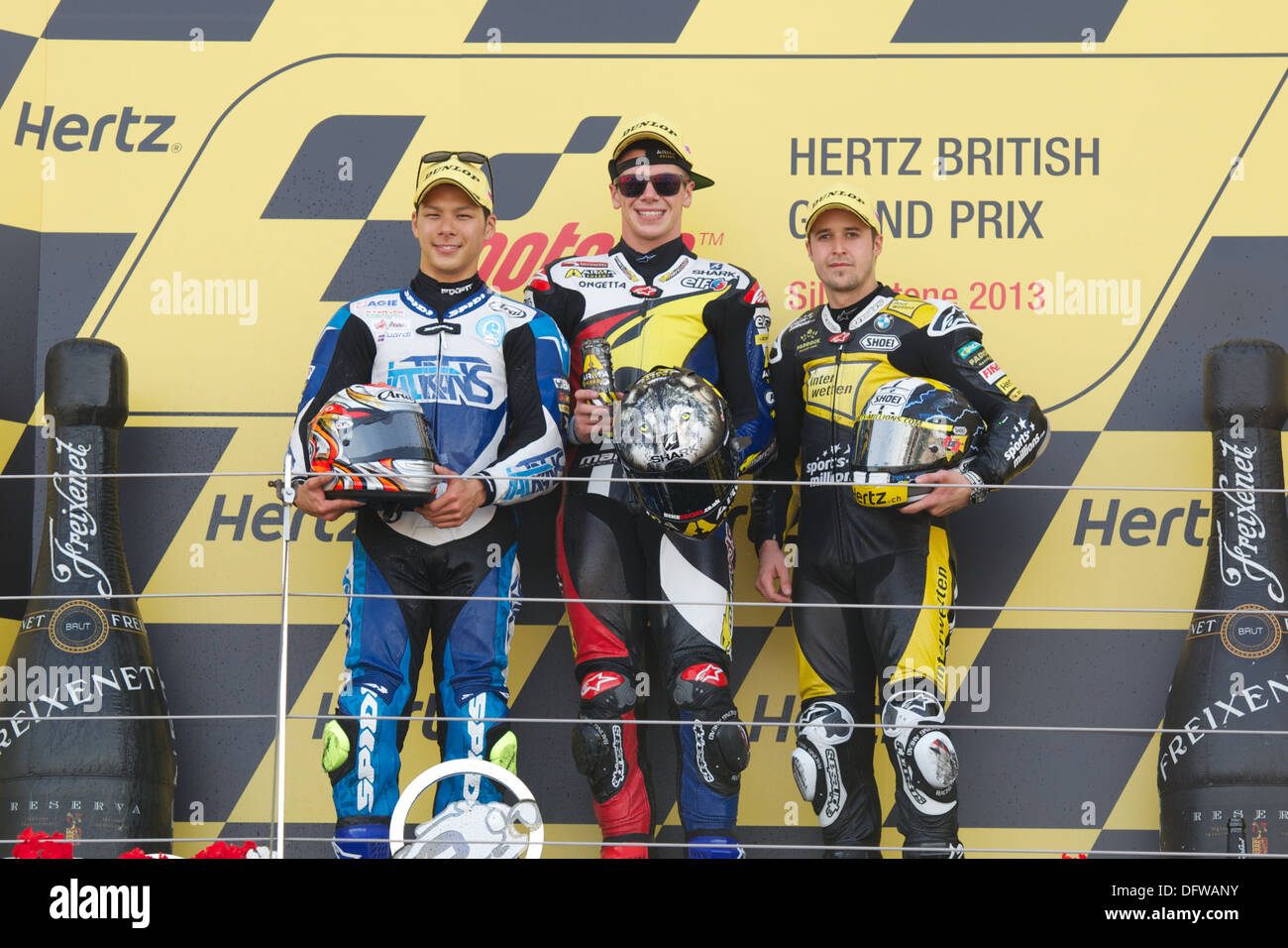 Scott Redding, Takaaki Nakagami and Thomas Luthi stand on the Silverstone Podium after winning the Moto2 race - Stock Image