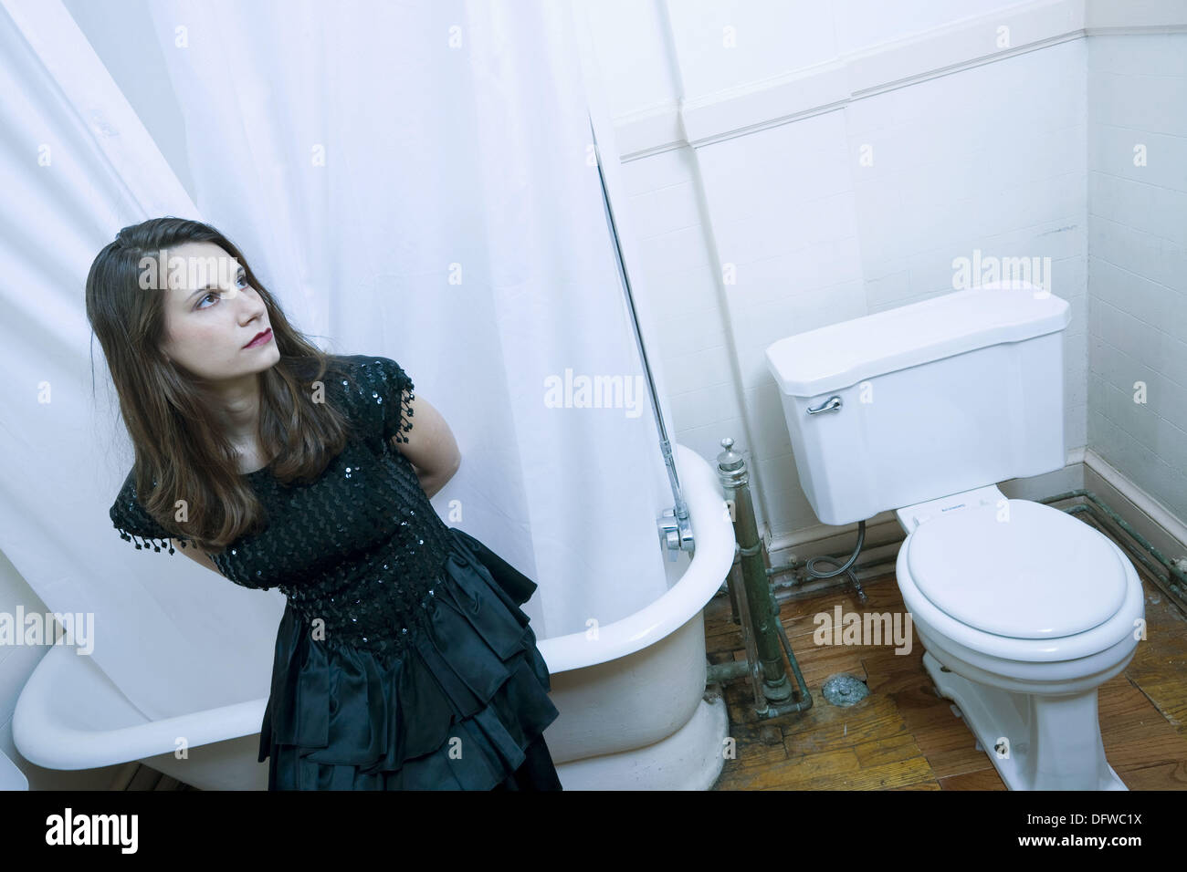 Young woman, in an evening dress, sitting on the edge of her bathtub ...