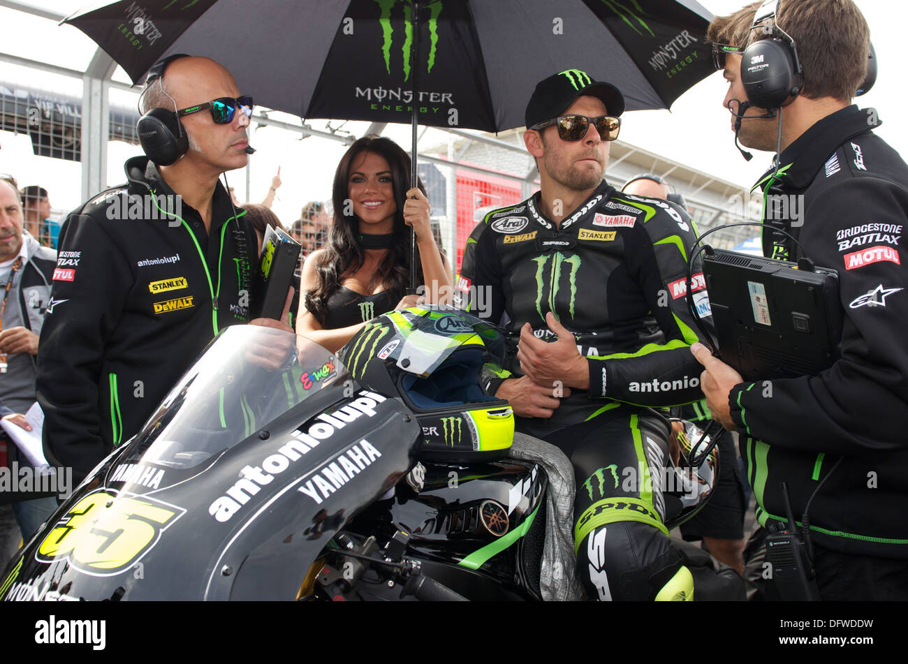 Monster Energy Grid Girl holds team umbrella for British MotoGP rider Cal Crutchlow during the British Grand Prix at Silverstone - Stock Image
