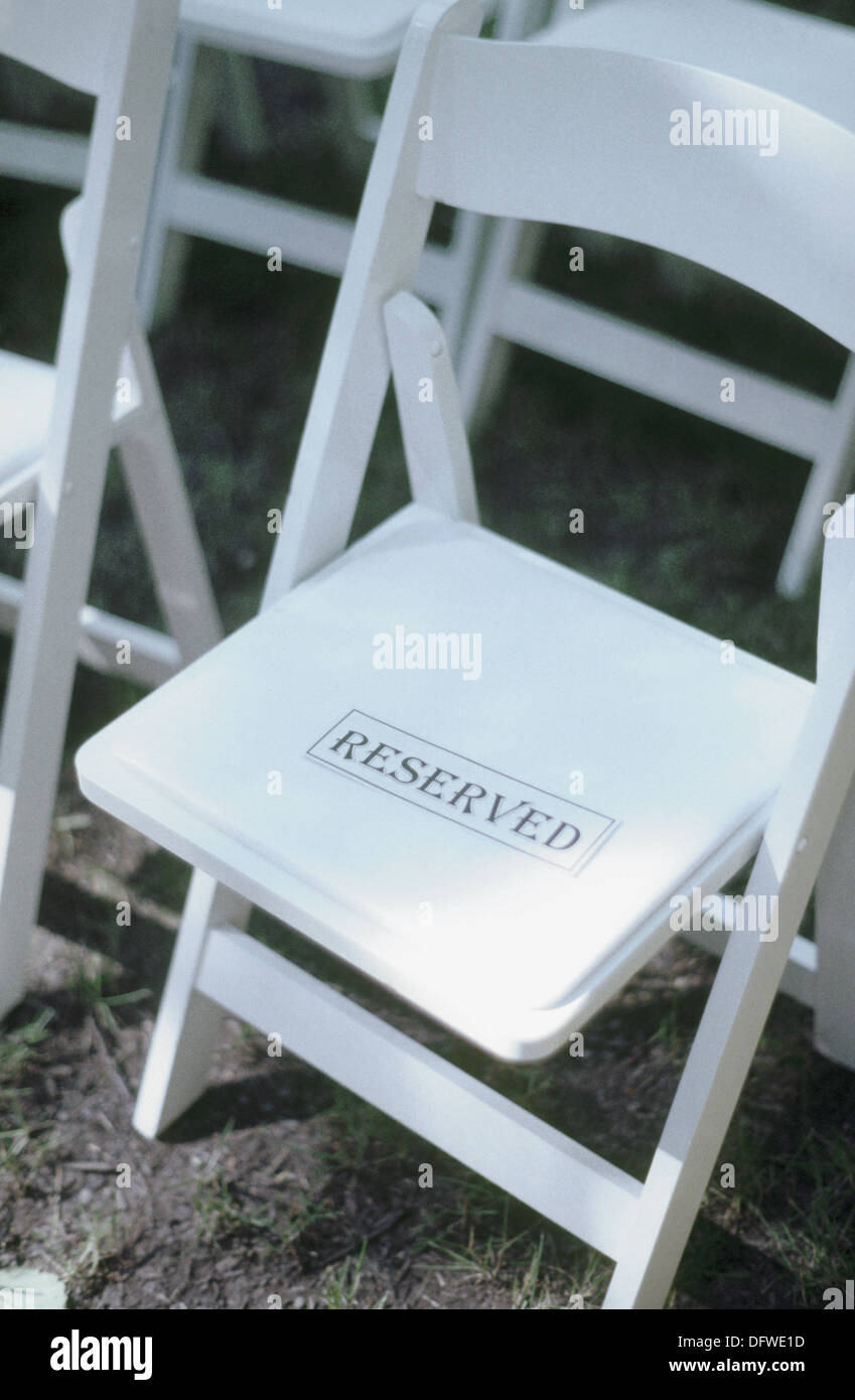 White wooden chair with ´reserved´ sign - Stock Image