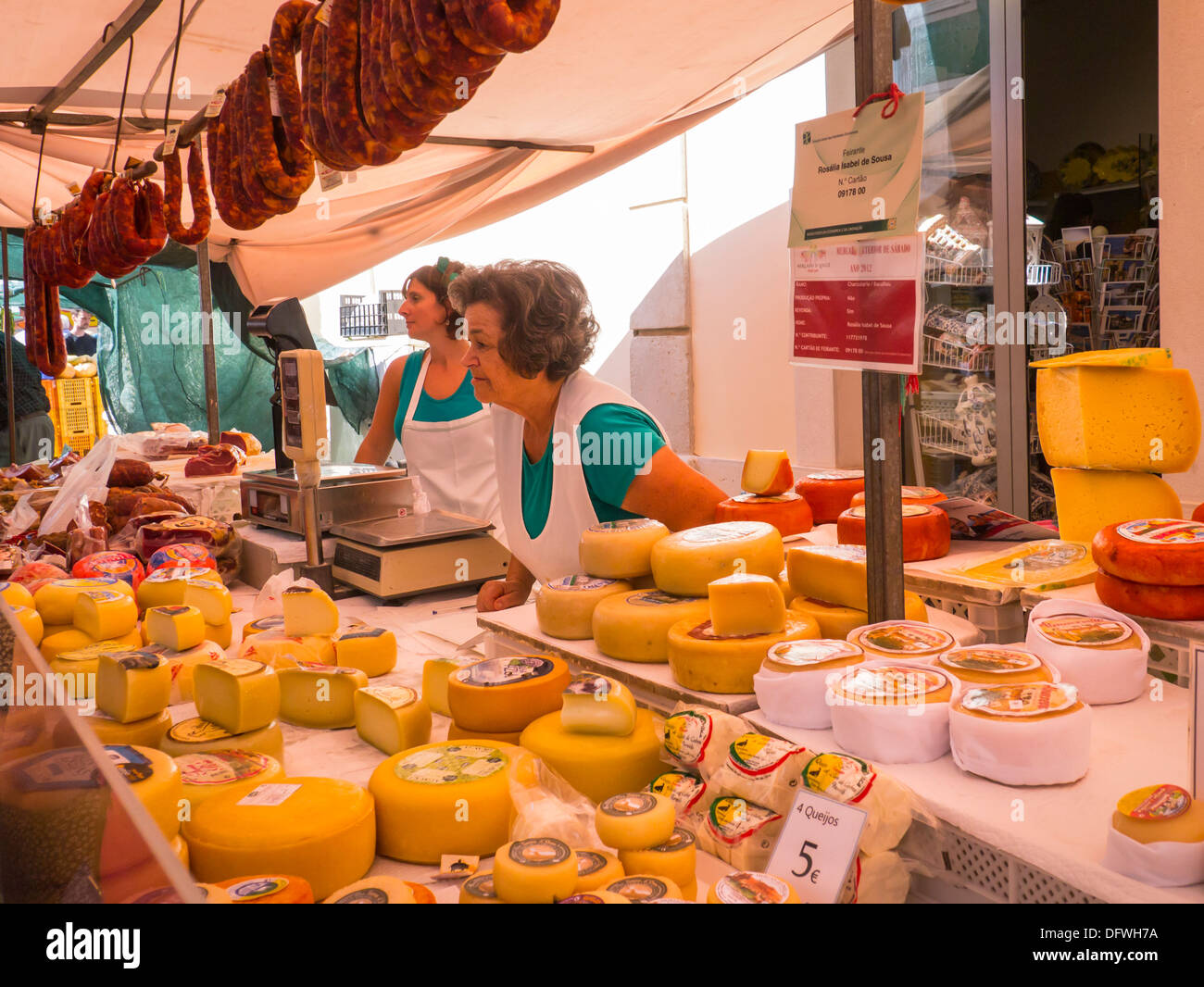 Portugal Algarve Loule market cheese cheeses stall chorizo spicy sausage sausages scale scales 2 ladies women serving scales weighing machine - Stock Image