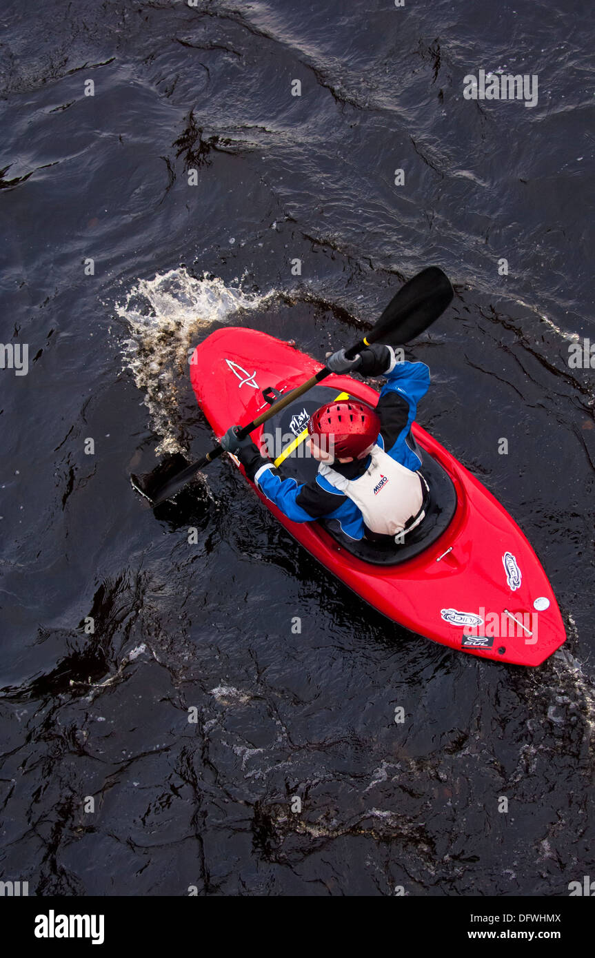 View of single red kayak with kayaker from above - Stock Image