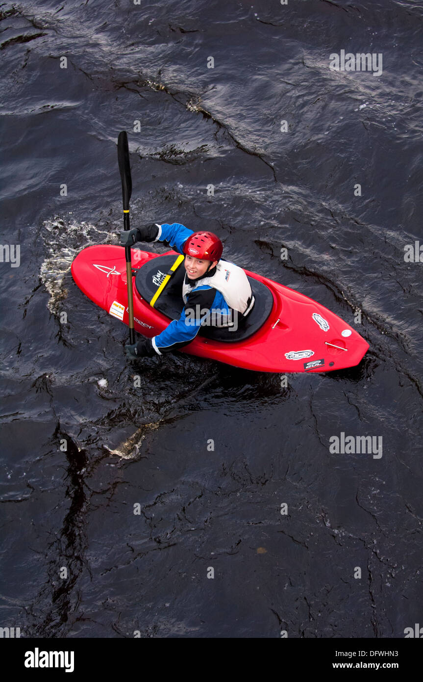 View of single red kayak with kayaker looking up towards camera from above - Stock Image