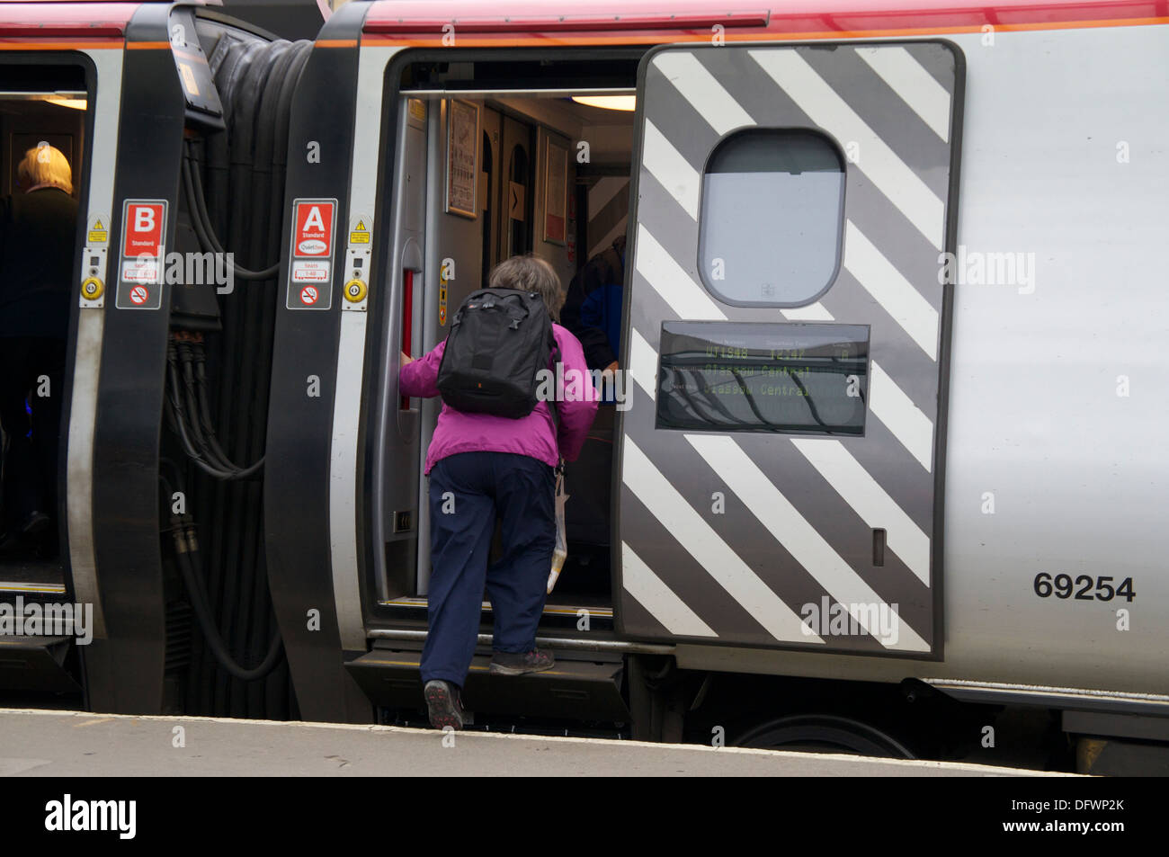 Woman passenger getting on a Virgin Pendolino at Carlisle Railway Station Carlisle Cumbria England United Kingdom Stock Photo