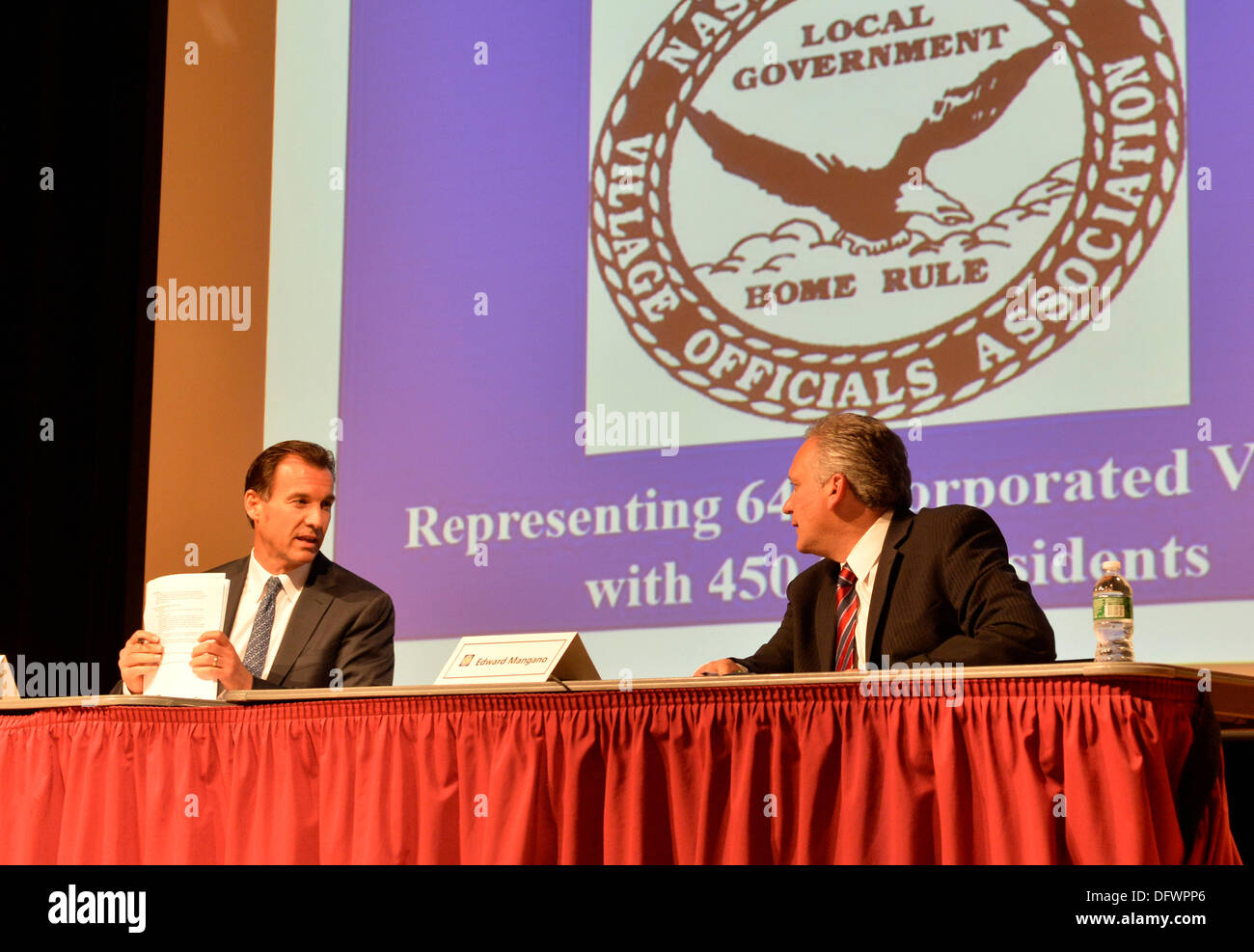 Old Westbury, New York, U.S. 8th October 2013. At table, R-L, Republican EDWARD MANGANO, the Nassau County Executive, and Democrat THOMAS SUOZZI, the former County Executive, face each other in a debate hosted by the Nassau County Village Officials Association, representing 64 incorporated villages with 450,000 residents, as the opponents face a rematch in the 2013 November elections. Credit:  Ann E Parry/Alamy Live News - Stock Image