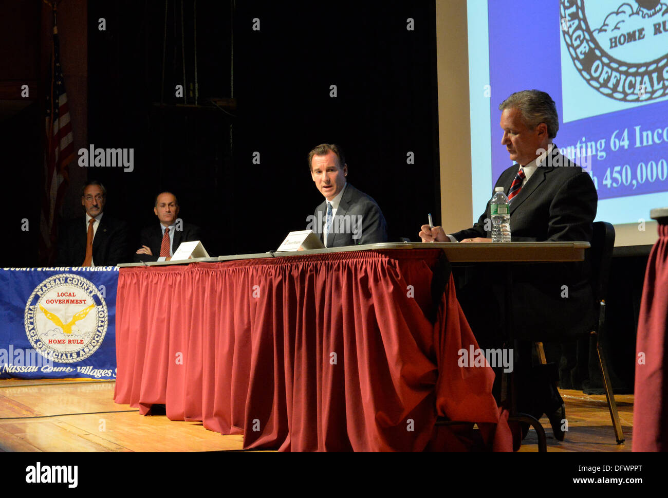 Old Westbury, New York, U.S. 8th October 2013. Republican EDWARD MANGANO, the Nassau County Executive, and Democrat THOMAS SUOZZI, the former County Executive, R-L at red table, face each other in a debate hosted by the Nassau County Village Officials Association, representing 64 incorporated villages with 450,000 residents, as the opponents face a rematch in the 2013 November elections. Credit:  Ann E Parry/Alamy Live News - Stock Image