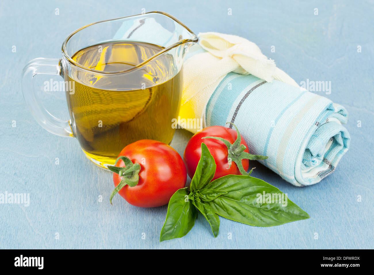 Olives, tomatoes, basil and towel on blue table - Stock Image