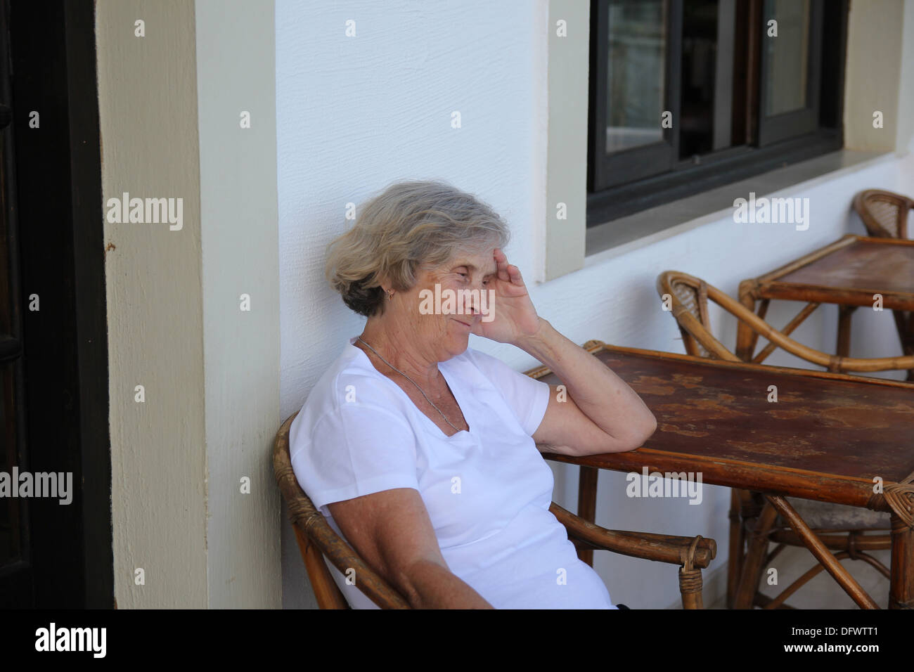 Smiling elderly woman sitting at the table - Stock Image