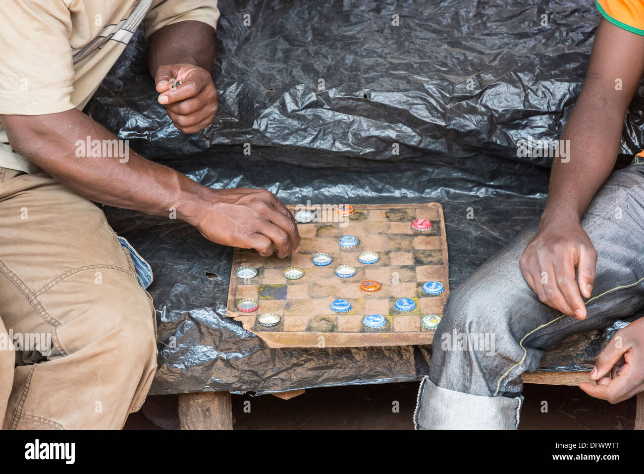 Two local men play draughts (checkers) on a home-made board using soft-drink bottle tops, Maramba Market, Livingstone, Zambia - Stock Image