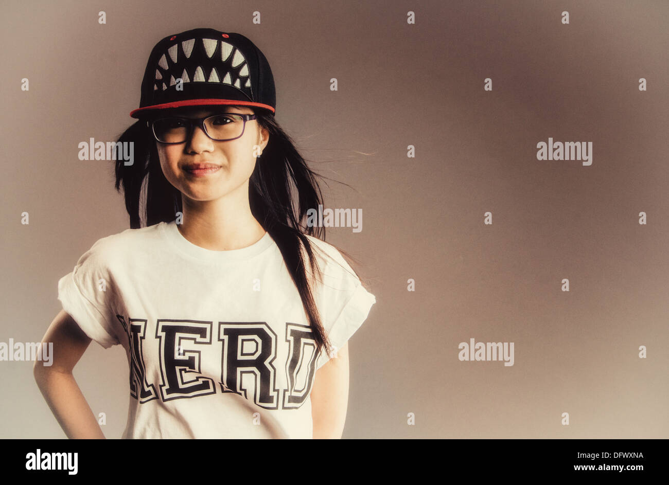 An Asian girl in a Nerd t-shirt and a baseball cap with teeth on - Stock Image