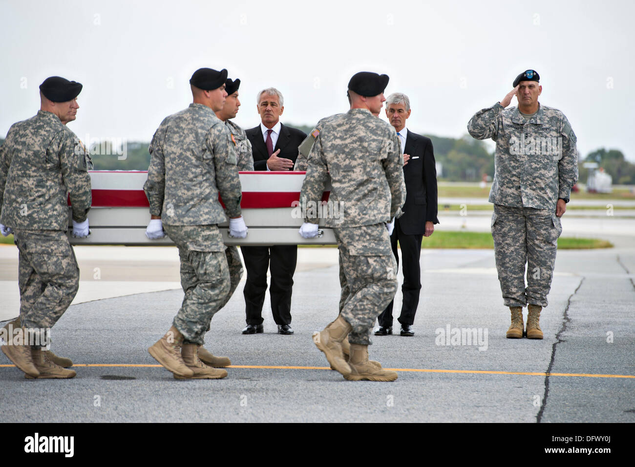 US Secretary of Defense Chuck Hagel, left, stands his hand over his heart with Secretary of the Army John McHugh and Army Chief General Ray Odierno as white-gloved soldiers carried the flag-draped case carrying the remains of Army Pfc. Cody from a C-17 cargo plane at Dover Air Force Base October 9, 2013 in Dover, DE.  Hagel announced that the Fisher House Foundation will provide the families of the fallen with the soldiers death benefits which cannot be paid by the Pentagon due to the government shutdown. - Stock Image