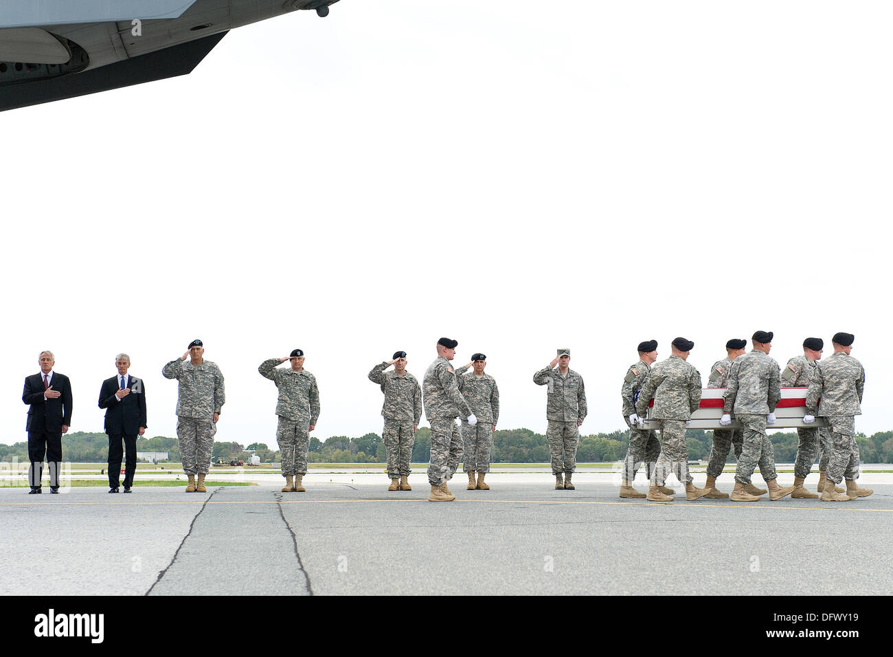 US Secretary of Defense Chuck Hagel, left, stands his hand over his heart with Secretary of the Army John McHugh and Army Chief General Ray Odierno and other military leaders as white-gloved soldiers carried the flag-draped case carrying the remains of Army Pfc. Cody from a C-17 cargo plane at Dover Air Force Base October 9, 2013 in Dover, DE.  Hagel announced that the Fisher House Foundation will provide the families of the fallen with the soldiers death benefits which cannot be paid by the Pentagon due to the government shutdown. - Stock Image