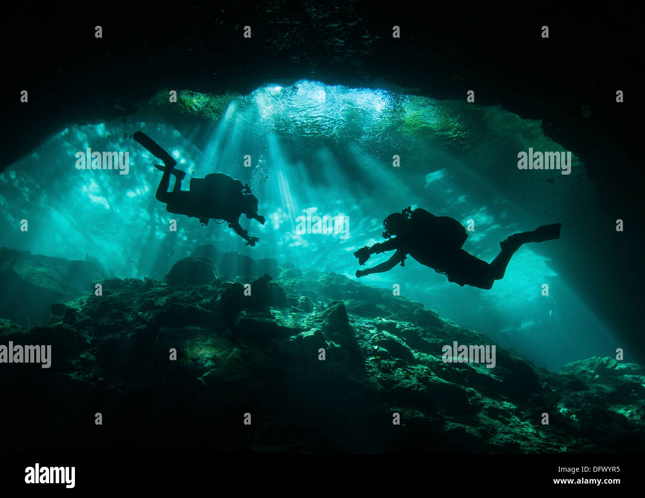Two divers silhouetted in light at entrance to Chac Mool cenote, Mexico. - Stock Image