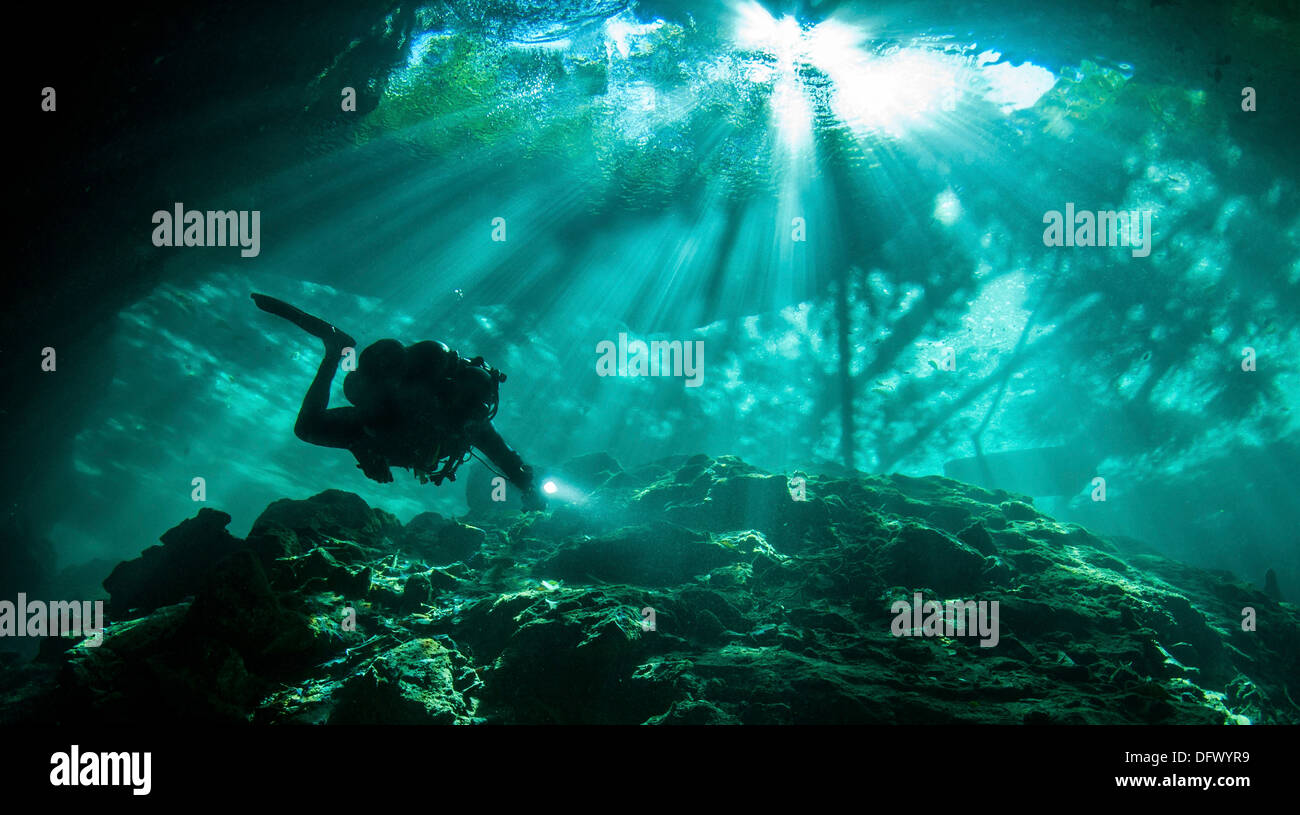 Diver passes through light beams in Chac Mool cenote in Mexico. - Stock Image