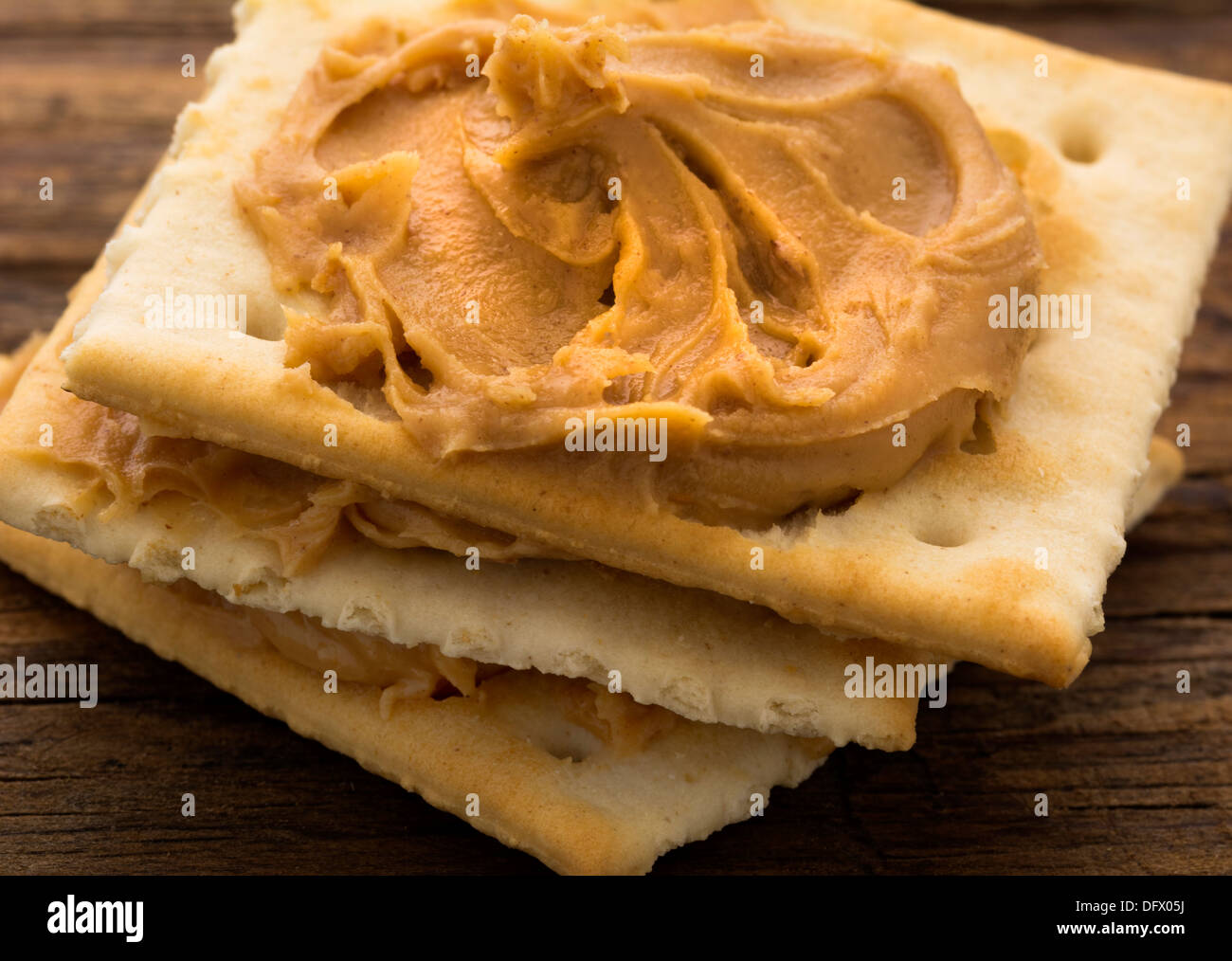 Peanut butter on crackers on weathered plank - Stock Image