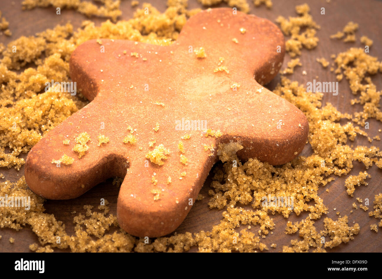 Brown sugar with clay man-shaped moisturizer on wooden plank - Stock Image