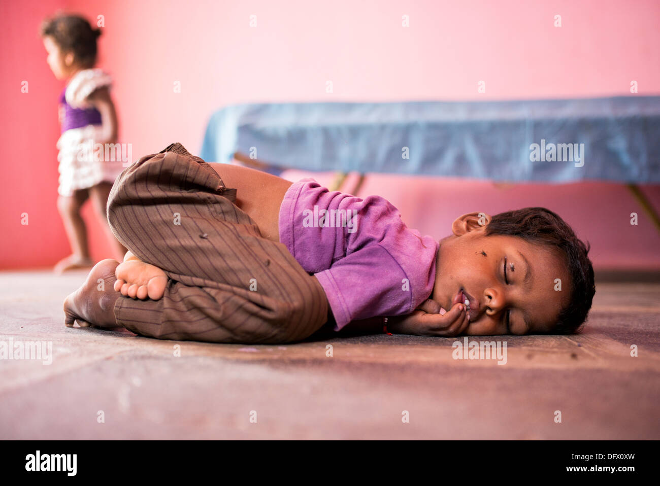 Small indian boy asleep on a stone floor in a rural indian village house. Selective focus. - Stock Image