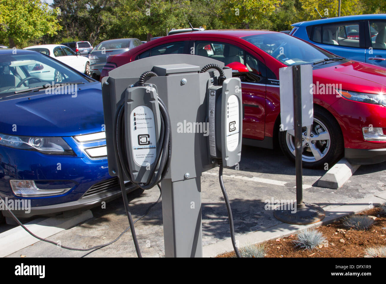 EV charging stations with plug-in electric cars plugged and charging their batteries in a workplace parking lot - Stock Image