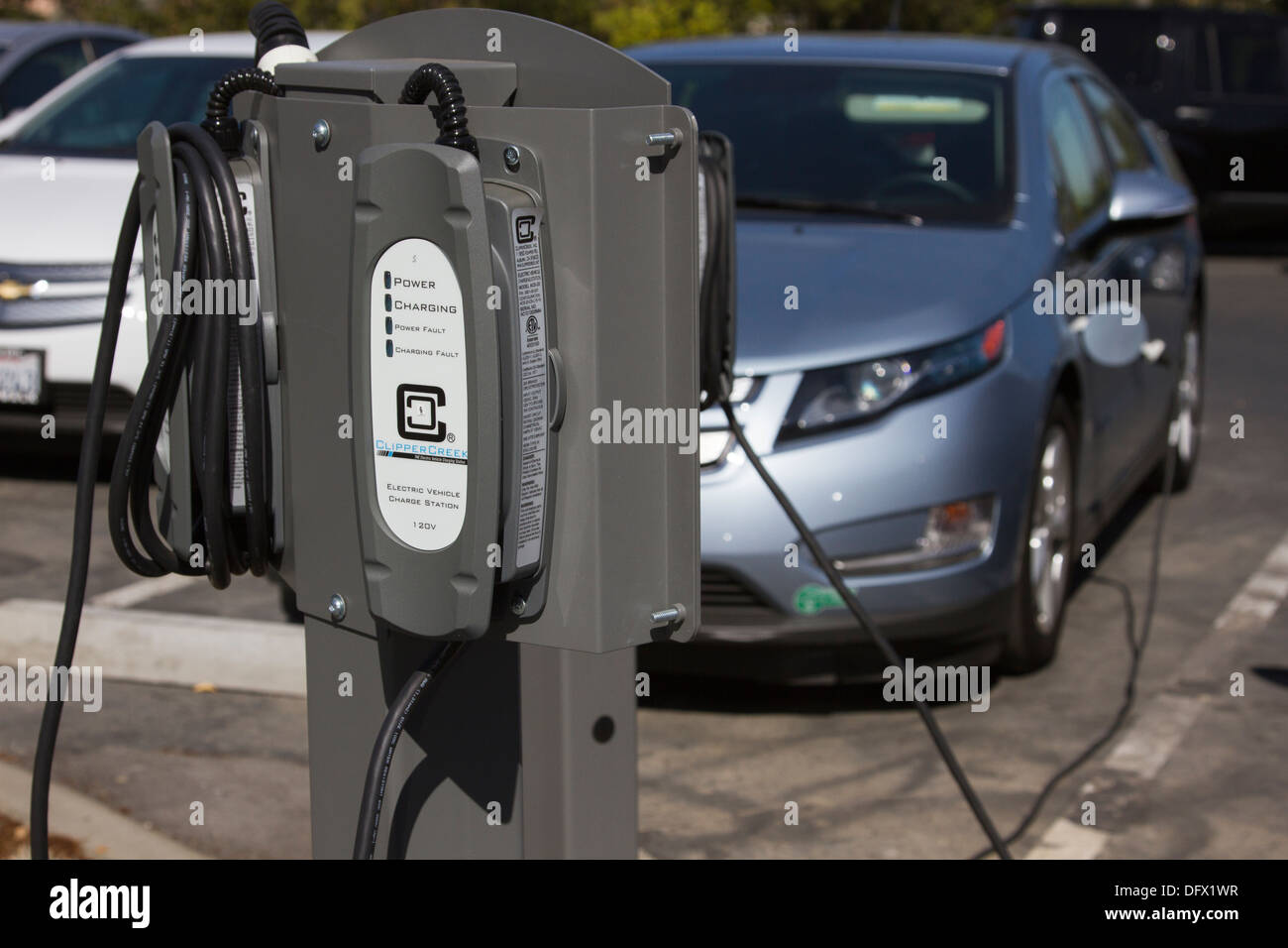 EV charging stations with plug-in electric car plugged and charging in at a company parking lot - Stock Image