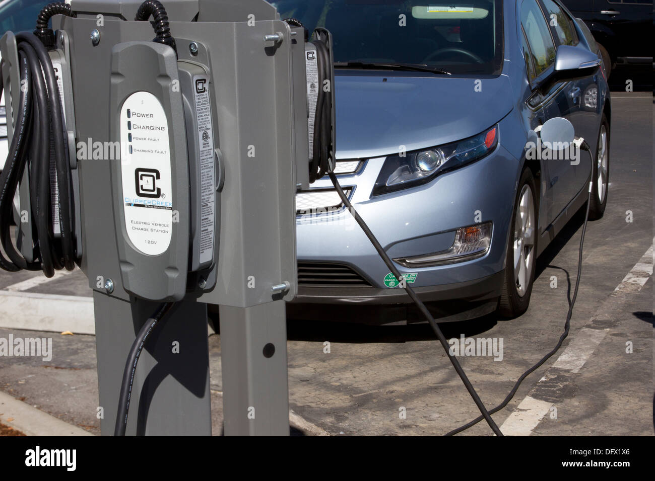 EV charging stations with plug-in electric car plugged to charge its battery in a workplace parking lot - Stock Image