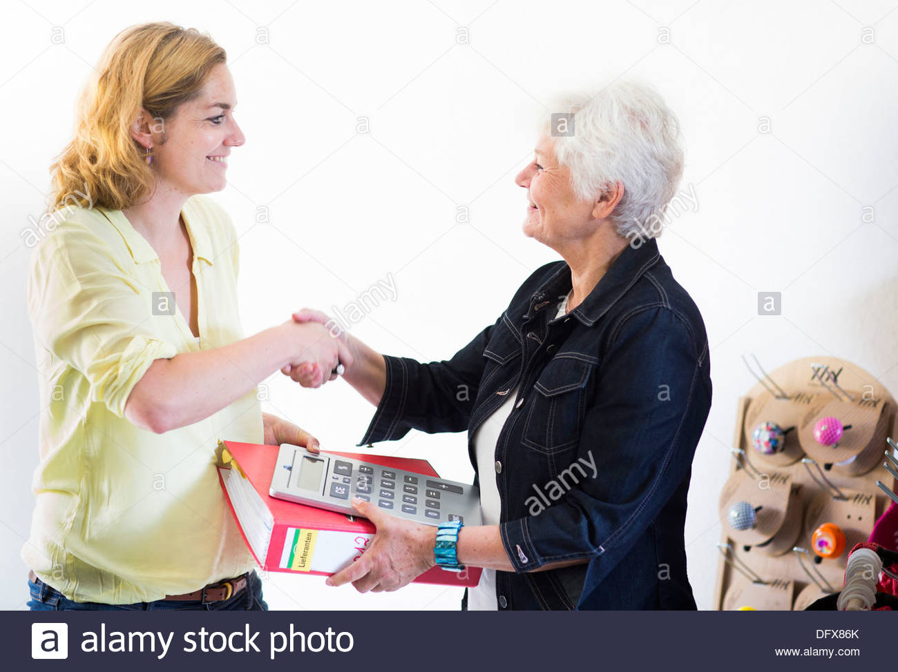 Mid adult woman shaking hands with an old woman - Stock Image