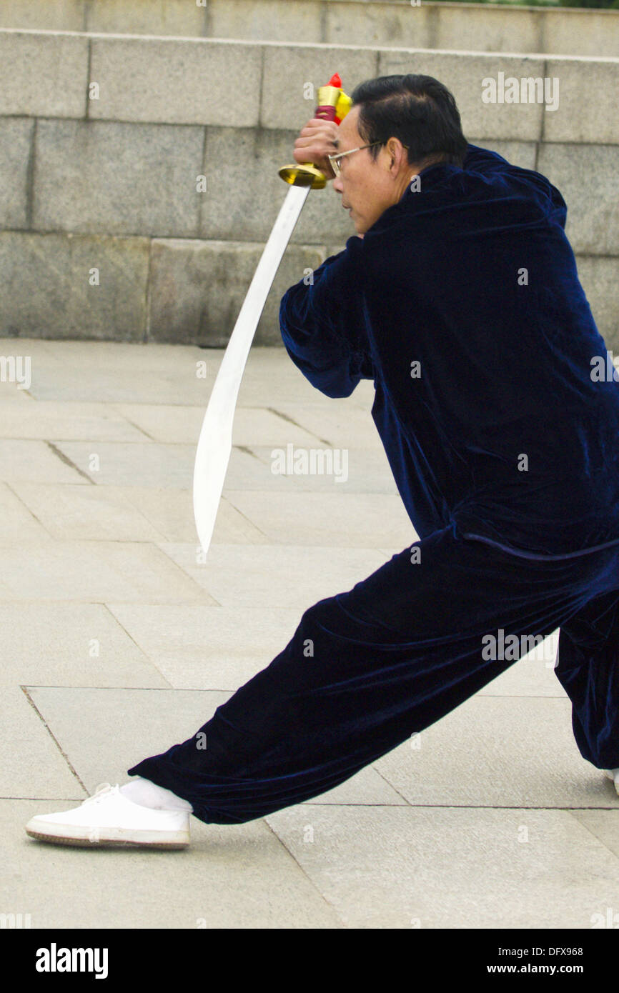 Chinese people practicing tai chi with swords in the early