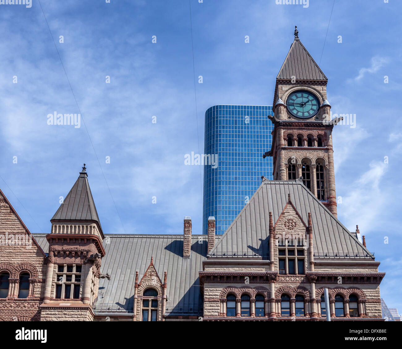 Romanesque revival style, sandstone old City Hall with clock tower and modern glass Skyscraper against a blue sky, Toronto - Stock Image