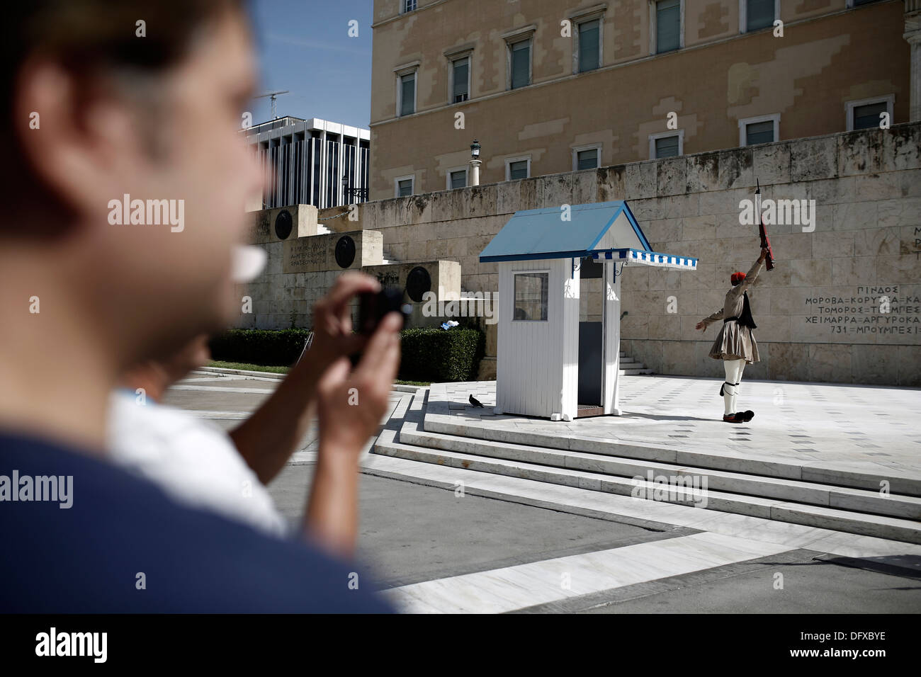 Tourists watching the changing of the guard ceremony at the Tomb of the Unknown Soldier in Syntagma Square in Athens, Stock Photo