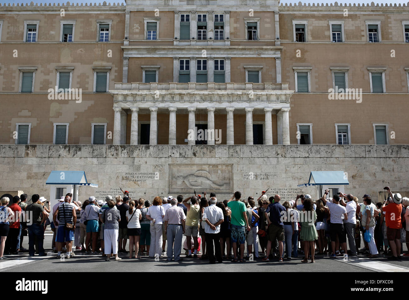 Tourists watching the changing of the guard ceremony at the Tomb of the Unknown Soldier in front of the Greek Parliament - Stock Image