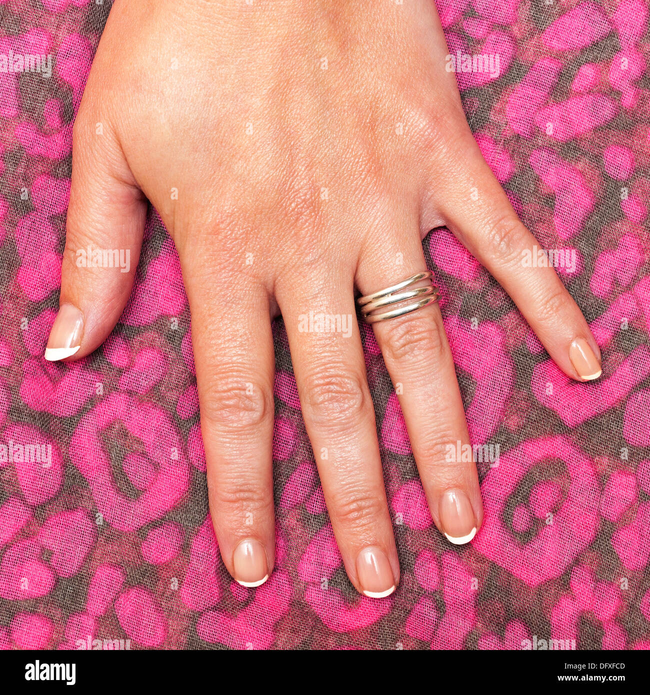 A close up of a womans hand with french polished nails - Stock Image