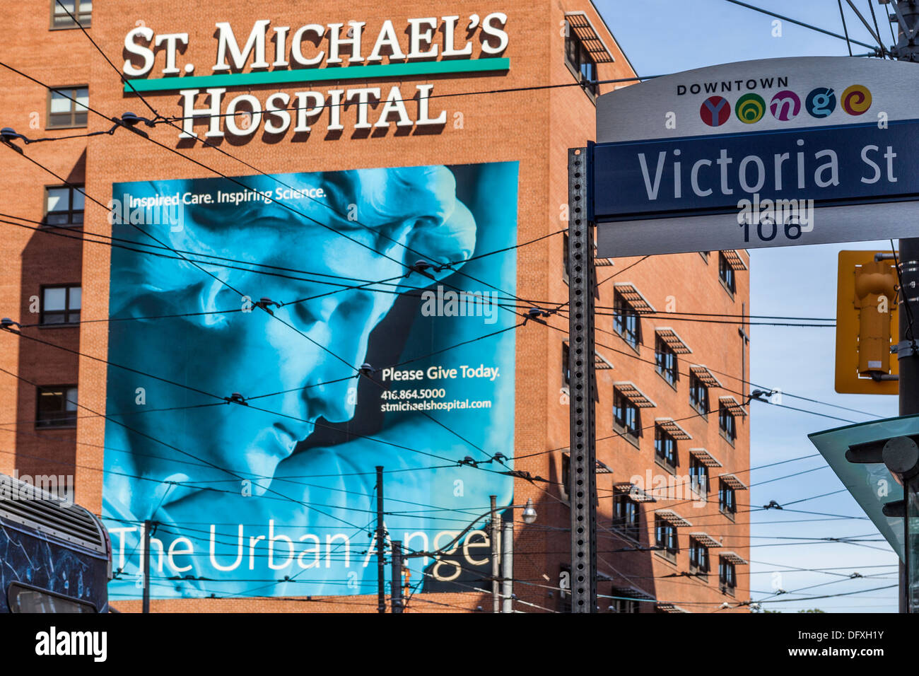 St Michael's hospital with mural and Victoria street sign in Downtown Yonge, Toronto - Stock Image