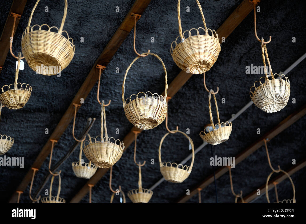 Small wicker basket hanging from a factory shop ceiling Camacha Madeira portugal - Stock Image