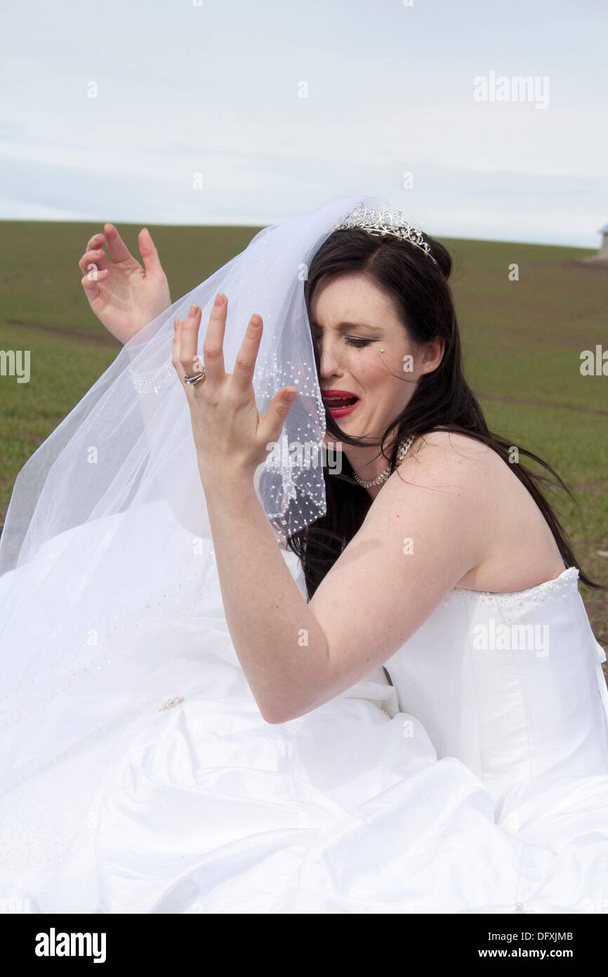 A young woman in a bridal gown, crying in a field Stock Photo ...