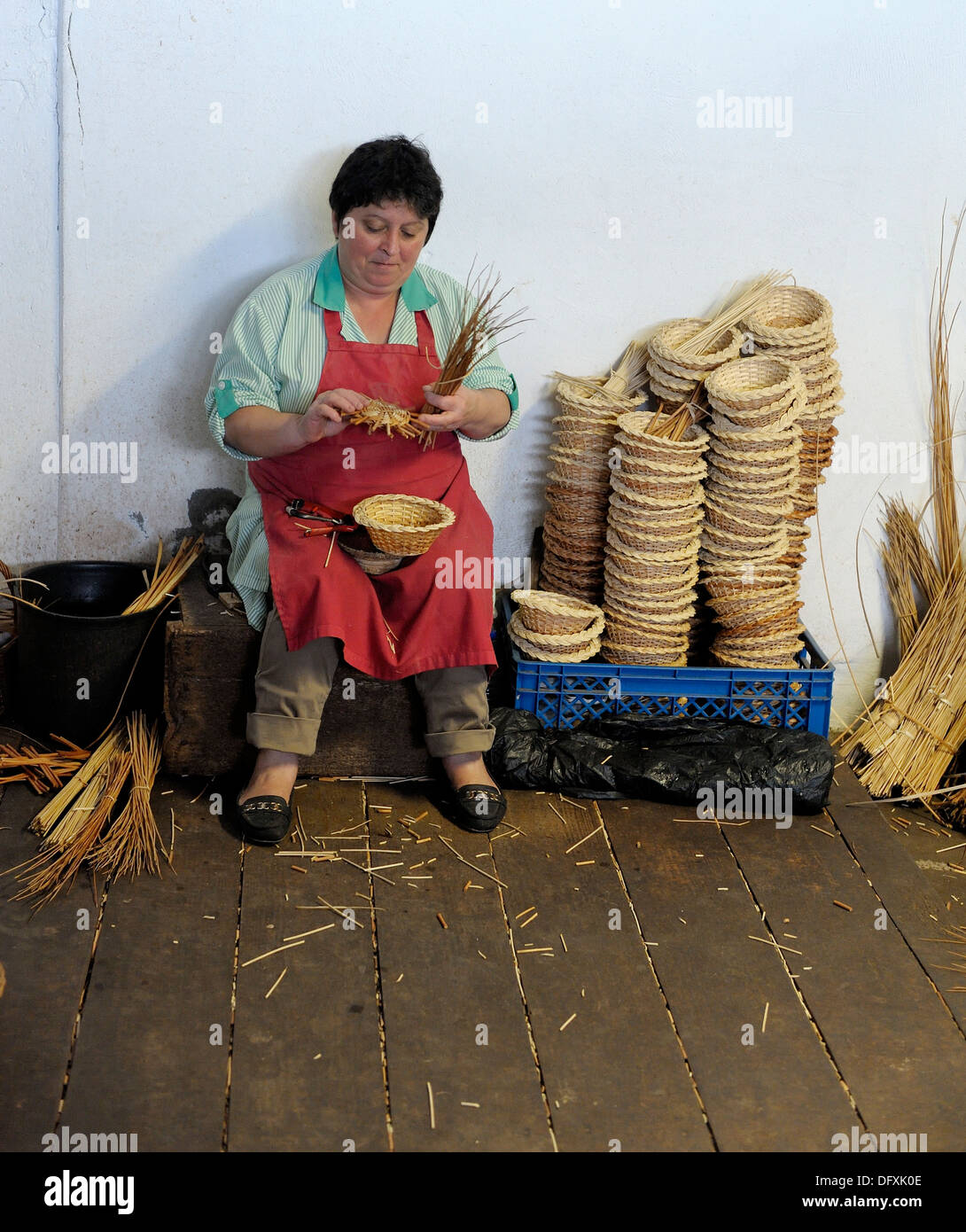 A Female basket weaver at work in the factory shop in Camacha Madeira Portugal - Stock Image