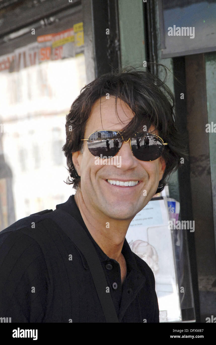 40-45 year old caucasian male, wearing sunglasses, close-up at an outdoor news stand. - Stock Image